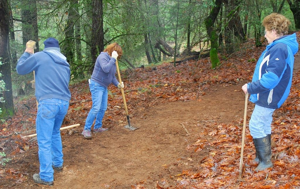 Photo of trail volunteers removing berms to outslope trails at Boggs Mountain Demonstration State Forest